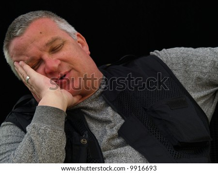 Sleeping or depressed man holding his head in his hand - stock photo