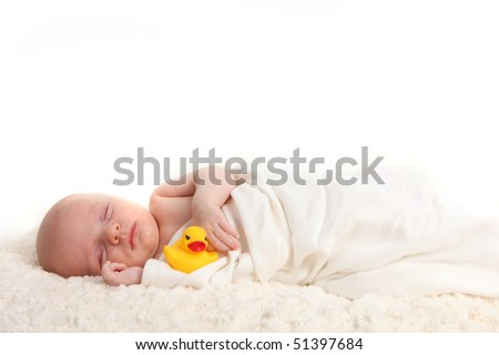 Sleeping Swaddled Infant Holding a Rubber Duckie on White Background - stock photo