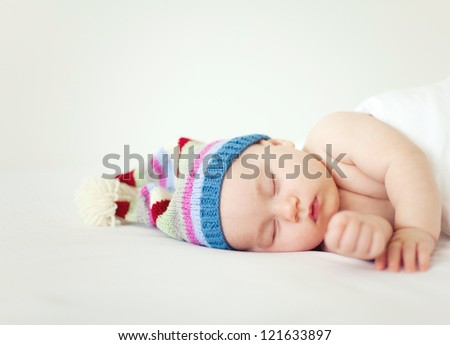 sleeping sweet baby wearing funny striped hat - stock photo