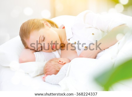 sleeping together and breastfeeding mother and her newborn baby in a white bed - stock photo