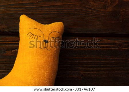 Sleeping toy cat on wooden background - stock photo