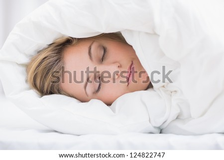 Sleeping woman hiding under the duvet in the bed - stock photo