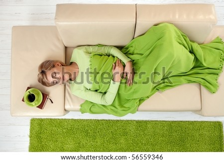 Sleeping woman in high angle view lying on sofa under blanket. - stock photo