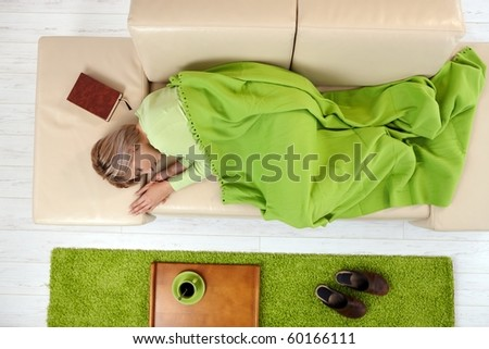 Sleeping woman in high angle view lying on sofa under blanket.? - stock photo