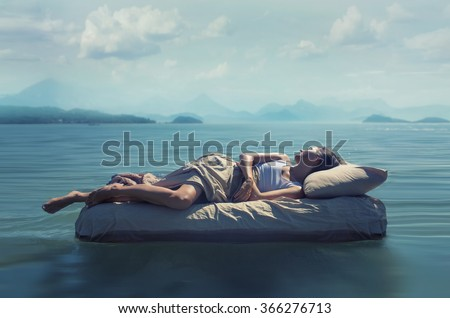 Sleeping woman lies on airbed in water. - stock photo