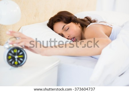 Sleeping woman stopping her alarm at home - stock photo