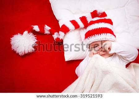 Sleepy baby on red blanket in knitted hat - stock photo