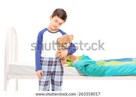Sleepy boy holding a teddy bear and standing in front of a his bed isolated on white background - stock photo