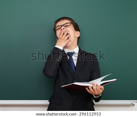 sleepy boy near the school board - stock photo