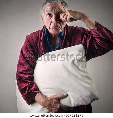 Sleepy elderly man with night-gown holding a pillow - stock photo