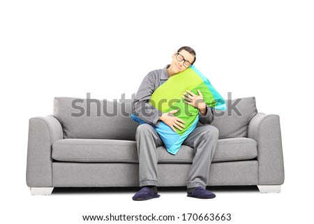 Sleepy guy in pajamas, sitting on sofa embracing a pillow, isolated on white background - stock photo