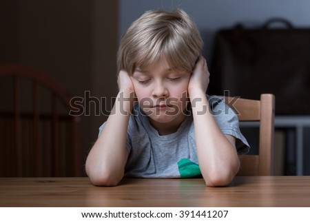 Sleepy little boy at the table needs some rest - stock photo