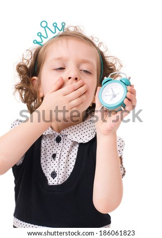 Sleepy little girl is holding wake up while yawning, isolated on white background - stock photo