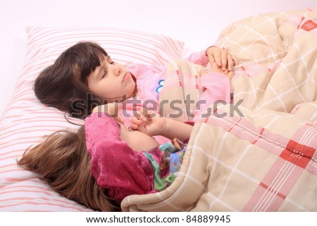 Sleepy little girls just waking up in bed, one still sleeps - stock photo