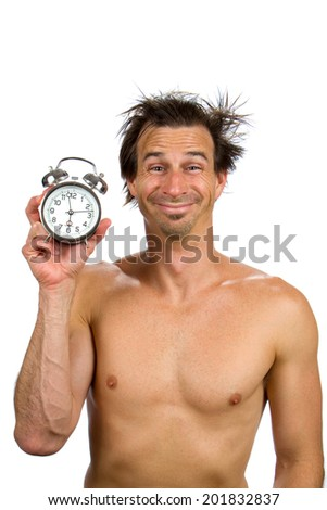 Sleepy man, with a goofy expression on his face, holds an old fashioned alarm clock after waking up in the morning. - stock photo