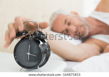 Sleepy mature man extending hand to alarm clock in bed at home - stock photo