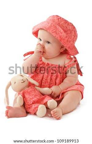 Sleepy 6 month old baby girl sits sucking her thumb and holds a stuffed toy bunny rabbit. Baby's strawberry pink floral hat and sun dress match the toy. Vertical, copy space, isolated on white. - stock photo