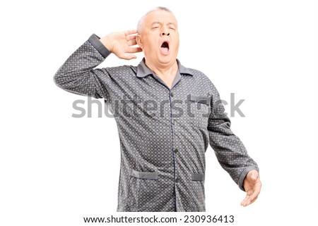 Sleepy senior in pajamas stretching on white background - stock photo