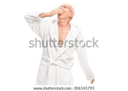 Sleepy senior man in a white bathrobe yawning isolated on white background - stock photo