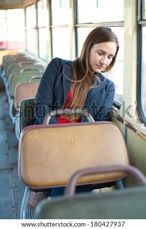 Sleepy woman resting in vintage bus - stock photo