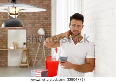 Sleepy young man leaning against wall, frowning with morning tea in hand. - stock photo