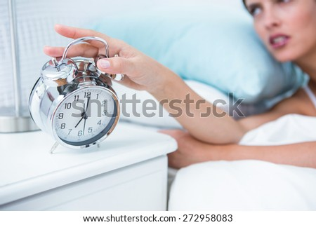 Sleepy young woman in bed extending hand to alarm clock at home in the bedroom - stock photo