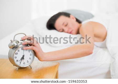 Sleepy young woman in bed with eyes closed extending hand to alarm clock at home - stock photo