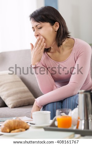 Sleepy young woman waking up on the sofa in the morning after a bad night's sleep, she is having breakfast and yawning - stock photo