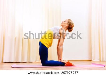 Slender athletic girl doing yoga exercises indoor. Stretching. - stock photo