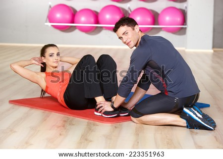 Slender fit young woman working out with a handsome male physical trainer at the gym toning her abdominal muscles - stock photo