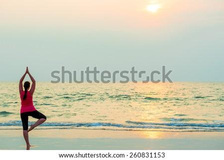 slender girl balancing on one leg. Yoga on the beach - stock photo