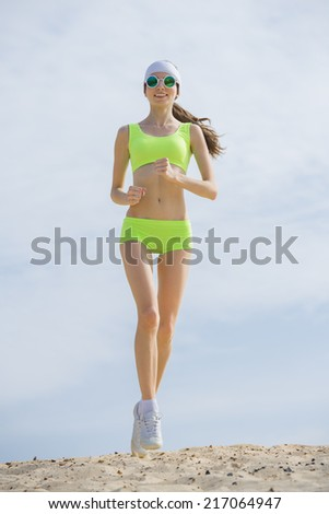 Slender girl in a  T-shirt is engaged in jogging on  beach - stock photo