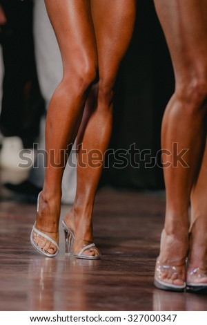 slender tanned female legs in high heels. woman to compete in fitness bikini - stock photo