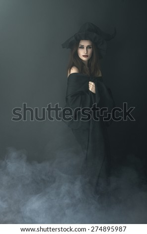 slender witch in a smoke on a black background - stock photo