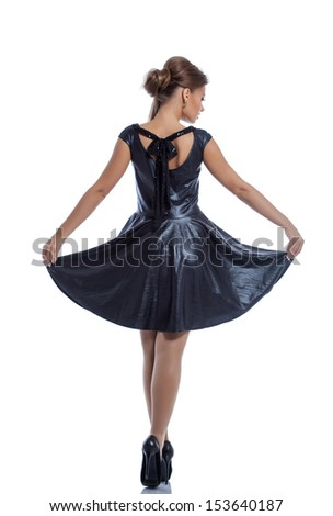 Slender woman in sexy dress posing back to camera - stock photo