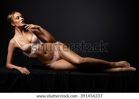 Slender young woman in a sexual pink lingerie lying on a floor over black background.  - stock photo