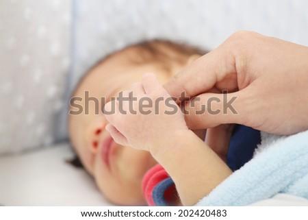 Slept baby hand holding mother finger  - stock photo