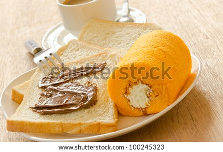 Slice bread with chocolate and cake roll - stock photo