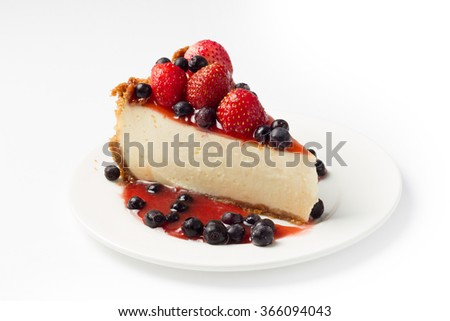 Slice cheesecake with strawberry and blueberries on white plate - stock photo