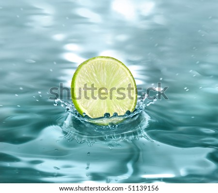 slice lime falling in a refreshing drink - stock photo