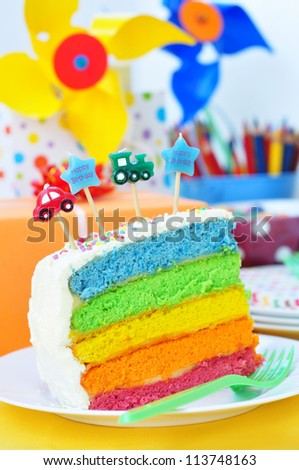 Slice of a birthday rainbow cake  for kids party - stock photo