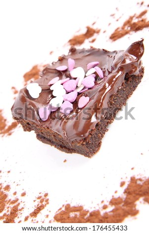 Slice of a brownie covered with chocolate and decorated with sugar hearts - stock photo