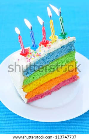 Slice of a layer rainbow cake - stock photo