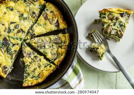 Slice of a spinach mushroom frittata sitting on white plate and fork next to cast iron skillet pan - stock photo