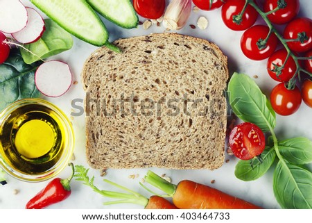 Slice of a whole wheat bread and healthy organic vegetables for making sandwiches. Healthy eating or cooking concept. - stock photo