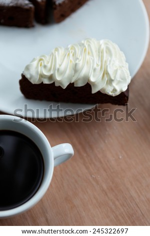 Slice of Belgium chocolate cake with whipped cream on the top with a cup of black coffee - stock photo