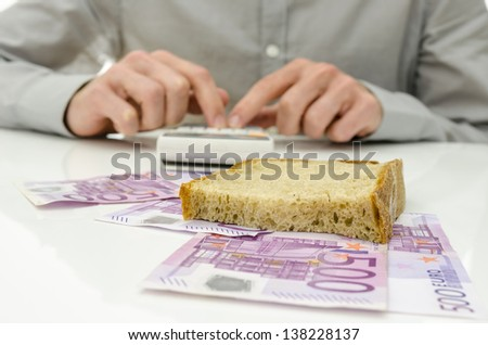 Slice of bread on Euro banknotes with male hand calculating food expenses in background. - stock photo