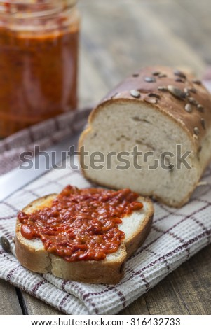 Slice of bread smeared with chutney on wooden table - stock photo