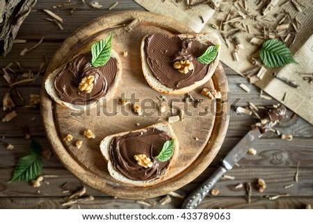 Slice of bread with chocolate cream and nuts. Chocolate spread with knife. Top view.  - stock photo