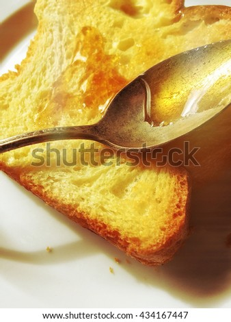 Slice of brioche toast with old spoon and honey - stock photo